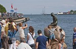 Tourists surround the Little Mermaid statue in Copenhagen Harbor