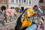 Children on Copenhagen's Stroget pedestrian street playing on decorated statues from the Elephant Parade street art exhibition.