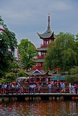 Bridge on Dragon Boat Lake in Tivoli Gardens amusement park with pagoda and roller coaster