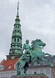 Equestrian statue of Bishop Absalon with St Nicholas Church steeple in Copenhagen