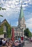 Kristiansand Cathedral in summer with downtown sidewalk restaurant nearby