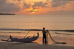 Fisherman on Jimbaran Beach at sunset, Bali, Indonesia.