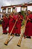 Tibetan monks playing traditional ceremonial musical wind instruments at temple near Lhasa