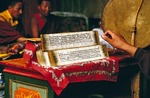 Tibetan scripture inside Lhasa's Jokhang Monastery being read by a monk.