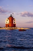 Round Island Lighthouse with wooden boat in Straits of Mackinac near Mackinac Island, Michigan, USA