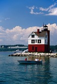 Boaters at Round Island Lighthouse with Mackinac ferry and Grand Hotel on Mackinac Island in background