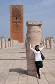 Moslem woman with column in square of mosque and Hassan Tower in Rabat, Morocco