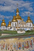 Golden-domed St. Michael's Cathedral in Kiev with mural on wall in foreground.