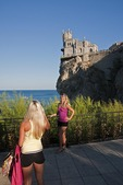 Ukrainian tourists taking photos at Swallow's Nest Castle overlooking the Black Sea on Aurora Cliff of the Ai-Tudor Cape near Yalta.