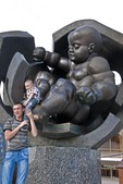Father and son posing with statue of giant baby that symbolizes the rebirth of city at seaport of Odessa.