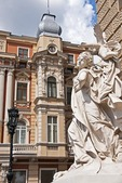 Statuary at entrance of Odessa National Academic Theater of Opera and Ballet with nearby facade of classic architecture.