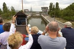 Passengers with cameras and iPad on Viking Lomonosov photographing cruise ship entering a lock on the Dnieper River in Ukraine.