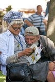 Elderly homeless couple sharing a literary moment in an Odessa park.