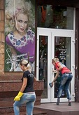 Young women preparing entrance to clothing shop for morning opening in downtown Zaporozhye, Ukraine.