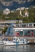 Yalta harbor waterfront with shops and Alexander Nevsky Cathedral in summer.