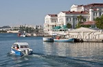 Aquarium on Sevastopol waterfront with pleasure boat passing.
