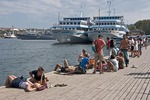 Young backpackers on Grafs Wharf in Sevastopol Harbor with naval ships and cruise ships in background.