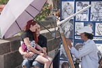 Sketch artist on Charles Bridge doing portrait of young couple.