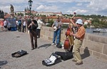 Charles Bridge musicians playing for tips from tourists.