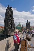Prague's Charles Bridge with organ grinder and tourists.