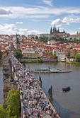 Charles Bridge crowded with pedestrians with Prague Castle above