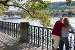 Couple along Vltava River with tour boat near Charles Bridge in Prague