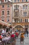 Restaurant patrons seated along Prague's Old Town Hall Square in summer