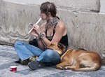 Young woman with her dog begging on street in Prague