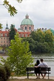 Young Prague couple on bench along Vltava River with St Francis of Assisi Church dome in background