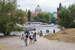 Prague tourists along Vltava River with St Francis of Assisi Church dome in background