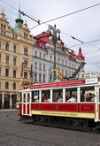 Tourists on sightseeing tour in historical tram through Old Town Prague