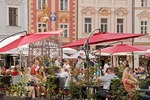 Restaurant patrons seated near Prague's Old Town Hall Square in summer.