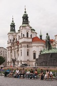 Tourists in Prague's Old Town Square with St Nicholas Church
