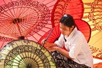 Young woman painting decorative designs at umbrella workshop in Old Bagan, Myanmar (Burma)