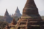 Climbing tourists exploring Bagan pagodas on Bagan Plains.