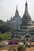 The golden Ananda Pahto Temple behind a stupa on the Bagan Plain.