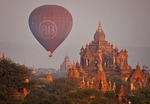 Tourist hot air balloon in flight over temple on Bagan Plain in morning in Myanmar.