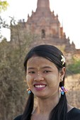 Young woman with thanaka-bark make-up with Bagan Buddhist temple in background.