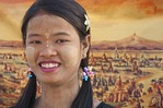Young woman with thanaka-bark make-up with painting of pagodas on Bagan Plains in background.