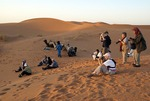 Tour group shooting at sunset in Sahara sand dunes.