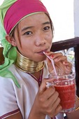 Young Padaung girl named Mimi enjoying strawberry juice near Indein village on Lake Inle in Shan State.