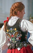 Folk dancer in Krakow's Main Market Square wearing traditional embroidered clothing.