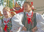 Folk dancers in Krakow's Main Market Square wearing traditional embroidered clothing.