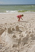 Girl with sand castle on Orange Beach of Alabama Gulf Coast.