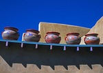 Decorative pottery jars displayed on wall in Taos, New Mexico.
