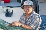 Vietnamese-American commercial shrimper mending nets on boat in marina at Biloxi on Mississippi Sound of Gulf Coast.