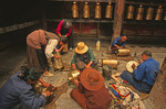 Jokhang Temple volunteers cleaning and polishing prayer wheels, Lhasa, Tibet.