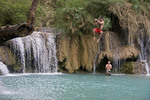 Tourists at Kuang Si Waterfall swinging over a limestone pool and swimming, near Luang Prabang, Laos.