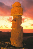 Rapa Nui (Easter Island) moai with red pukao topknot, lit at night.