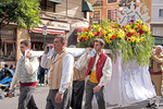Las Fallas Festival men in parade carrying float of flowers to the statue of the virgin.